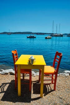 Café tableon beach dans la ville d'adamantas sur l'île de milos avec la mer égée avec des bateaux en arrière-plan