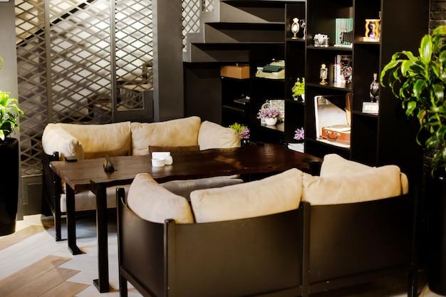 Café avec tables basses canapés confortables plantes et étagères