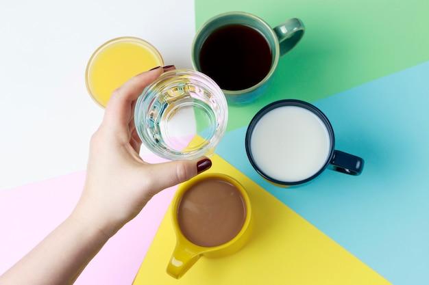 Café, thé et autres boissons dans des tasses colorées sur blanc