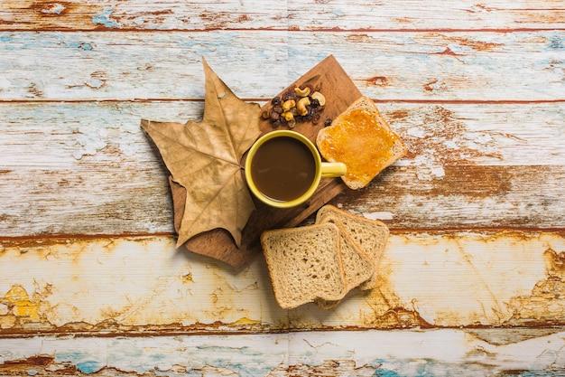 Café et toasts près des feuilles et des raisins secs
