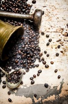 Café torréfié à grains dans un mortier avec pilon. sur fond rustique.