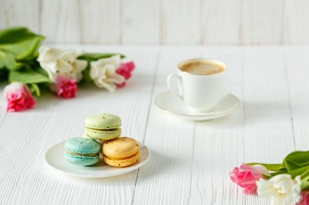 Café, tulipes roses et blanches et macarons sur la table en bois blanche. petit-déjeuner. pause café.