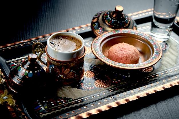 Café turc classique, fait dans le sable, servi sur un plateau national avec des ornements, des biscuits et de l'eau. table sombre