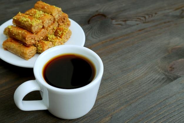 Café turc sur table en bois avec des pistaches pâtisseries baklava