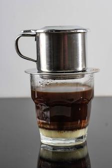 Café vietnamien avec lait concentré dans des tasses en verre et cafetière traditionnelle en métal phin. méthode traditionnelle de fabrication de l'égouttement de café vietnamien. espace pour le texte ou la publicité