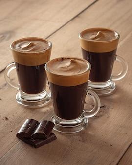 Cafés avec mousse et morceaux de chocolat sur fond de bois