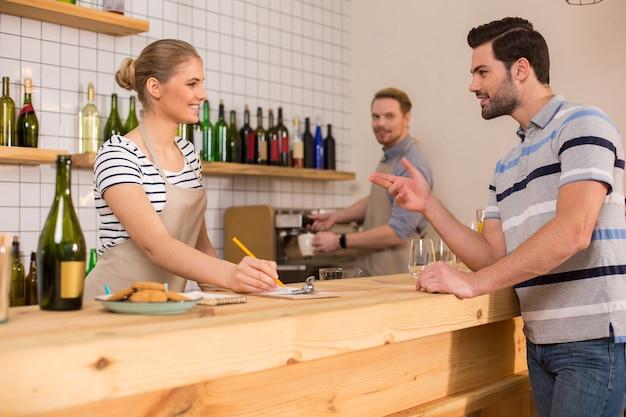 À la cafétéria. ravi bel homme affamé debout près du comptoir et commander de la nourriture tout en visitant une cafétéria