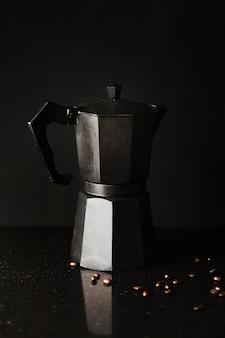 Cafetière avec grains de café sur fond noir