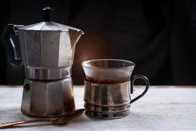 Cafetière en métal et café noir en coupe vintage, fond noir