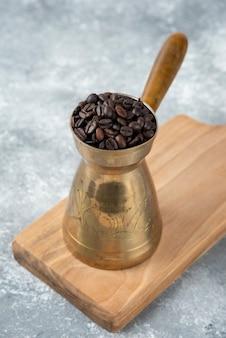 Cafetière pleine de grains de café torréfiés sur planche de bois.