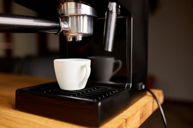 Cafetière prête à préparer un café. tasse de café en cours de préparation à l'aide d'une machine à expresso dans un café.