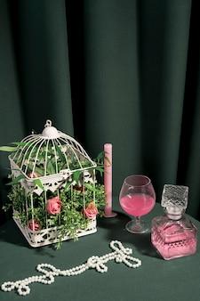 Cage blanche avec des fleurs à côté de l'arrangement girly