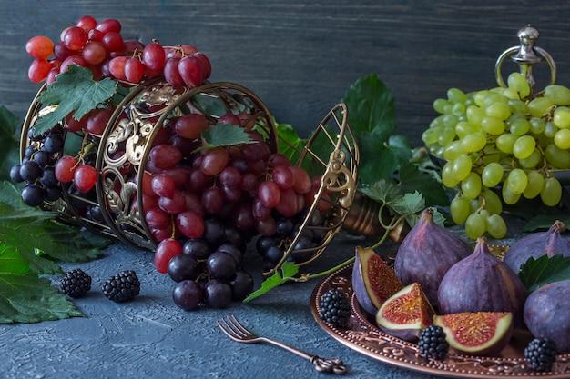 Cage décorative et raisins et figues rouges, clairs et foncés dans une assiette en bronze, une fourchette et des feuilles de vigne