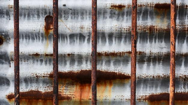 Cage en métal rouillé devant un vieux mur en métal.