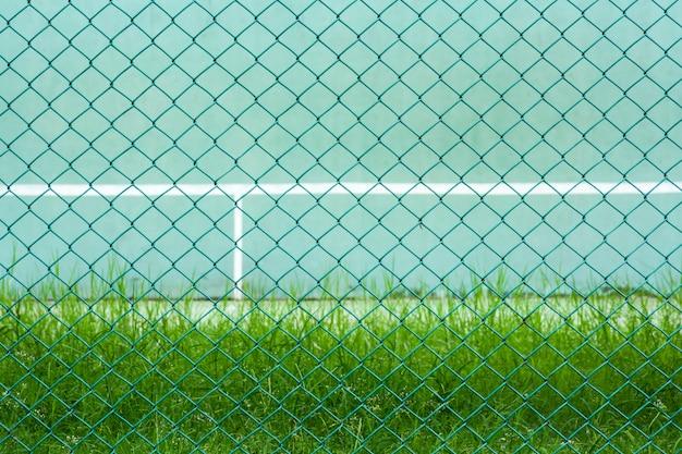 Cage métallique verte devant le court de tennis vert et le mur pour la pratique