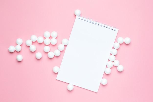 Cahier d'affaires et boules en plastique blanc rose