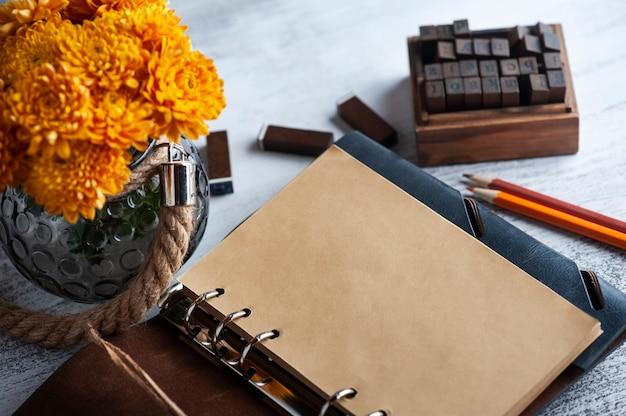 Cahier artisanal ouvert vide et fleurs de chrysanthème orange sur fond rustique. carte de voeux avec espace de copie pour votre texte