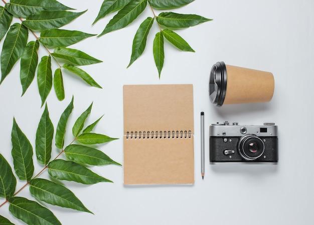 Cahier d'artisanat avec crayon, tasse à café, appareil photo rétro sur fond blanc avec des feuilles vertes. concept d'unité avec la nature. vue de dessus