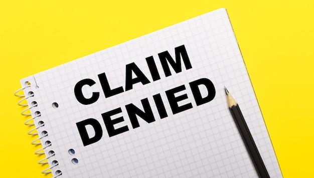 Cahier blanc avec claim denied écrit au crayon noir sur un mur jaune vif.