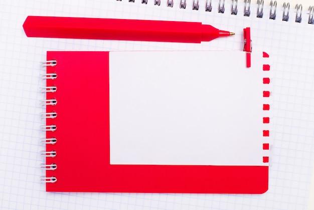 Sur un cahier blanc, il y a un stylo rouge, un bloc-notes rouge et une feuille de papier blanche avec un emplacement pour insérer du texte. modèle.
