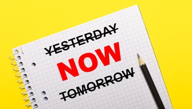 Cahier blanc avec inscription hier maintenant demain écrit au crayon noir sur fond jaune vif