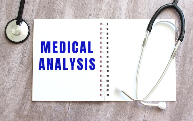 Un cahier blanc avec les mots analyse médicale et un stéthoscope sur une table en bois grise.