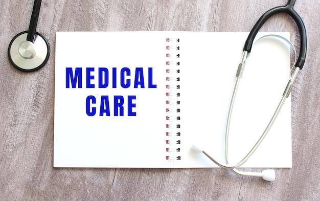 Un cahier blanc avec les mots soins médicaux et un stéthoscope sur une table en bois grise. notion médicale