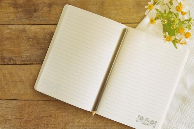 Cahier blanc ouvert sur une table en bois rustique avec un crayon