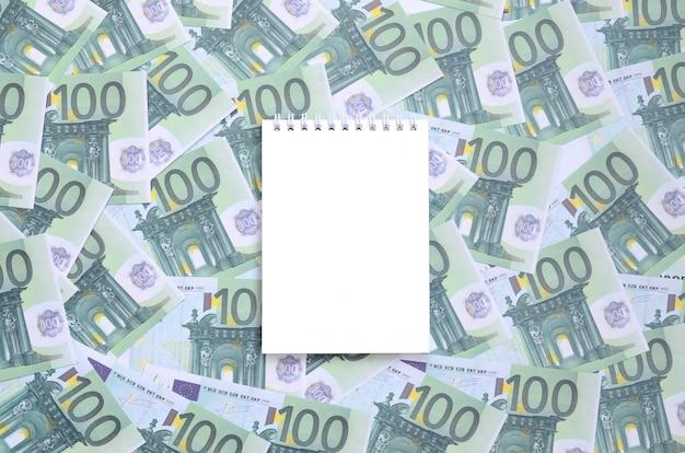 Cahier blanc avec des pages propres se trouvant sur un ensemble de billets verts