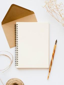 Cahier blanc avec une plume en bois sur une enveloppe brun pâle avec un fil marron et une branche sur un fond blanc
