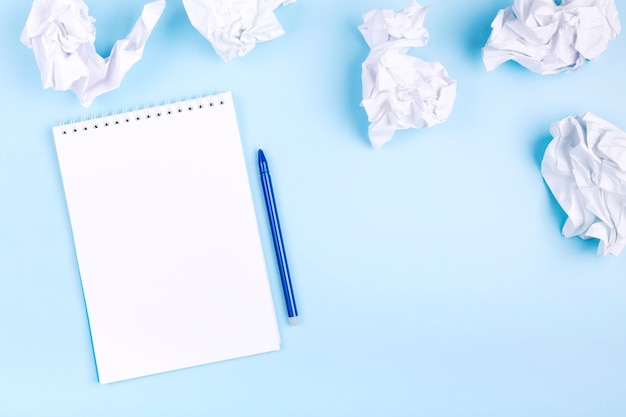 Cahier blanc et stylo sur fond bleu autour de papier froissé. concept de commencer à élaborer un plan, en rejetant les mauvaises idées.