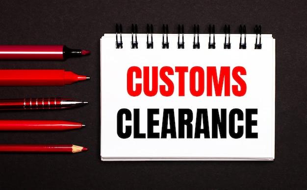 Un cahier blanc avec le texte customs clearance à côté de stylos, crayons et marqueurs rouges sur fond noir.