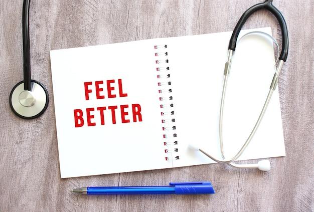 Cahier blanc avec texte rouge feel better et un stéthoscope sur une table en bois grise.