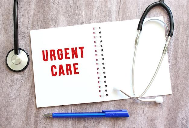 Cahier blanc avec texte rouge urgent care et un stéthoscope sur une table en bois grise.