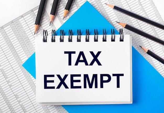 Cahier blanc avec le texte tax exempt sur la table à côté de crayons noirs sur fond bleu et de rapports. concept d'entreprise