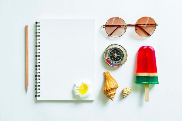 Cahier blanc vierge avec un crayon et des accessoires de voyage sur fond blanc.
