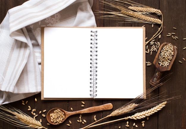 Cahier et blé sur une serviette avec une vieille table en bois