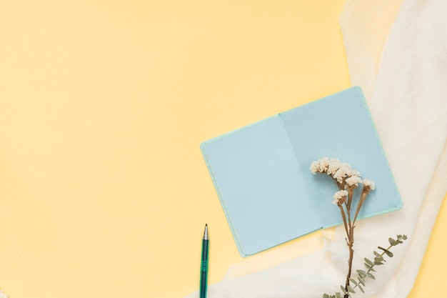 Cahier avec une branche de fleurs et un stylo