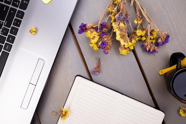 Cahier, café et fleurs pour femme ou bureau à domicile sur bois. vue de dessus. fond