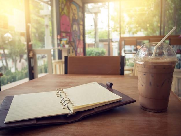 Cahier et café glacé sur fond en bois