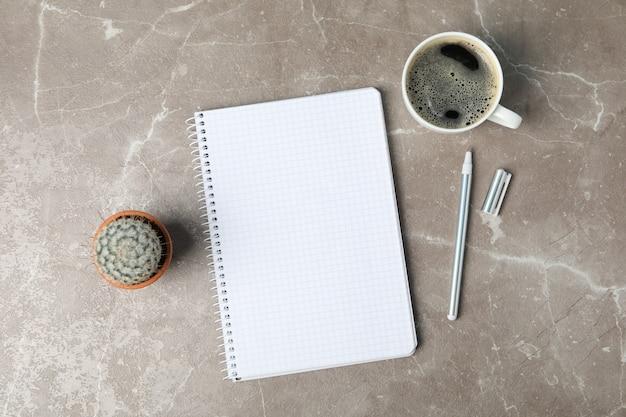 Cahier, café, stylo et cactus sur une surface grise