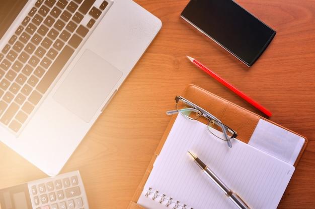 Cahier avec calculatrice, clavier et stylo sur table