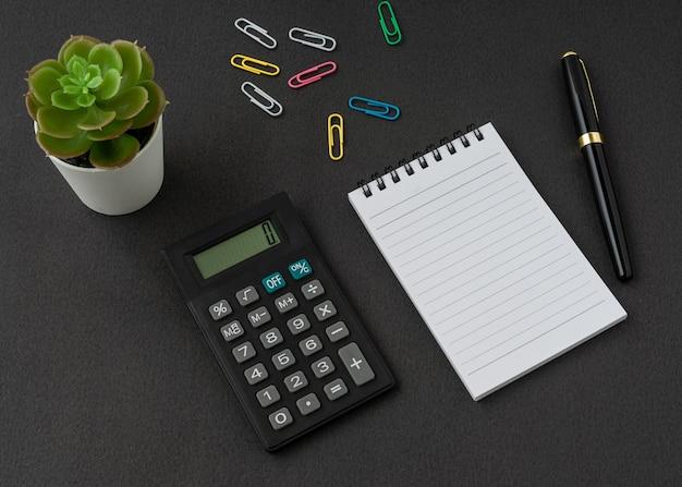 Un cahier, une calculatrice et un stylo sur une surface noire avec un espace de copie. concept commercial et financier.
