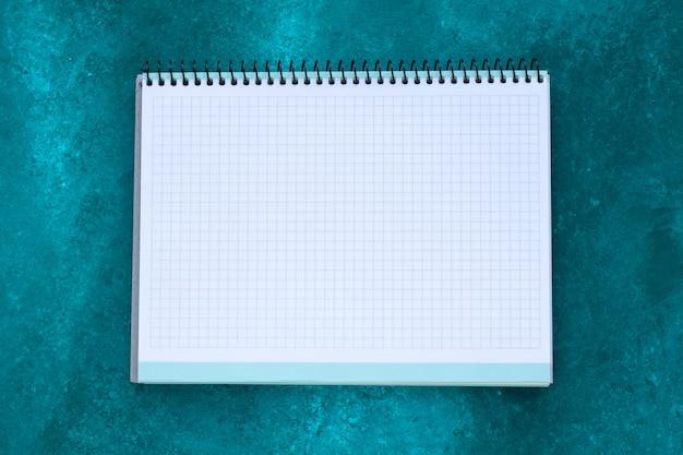 Cahier carré vide avec copie espace pour le texte sur fond peint vert abstrait. concept de planification. feuille de papier blanc.