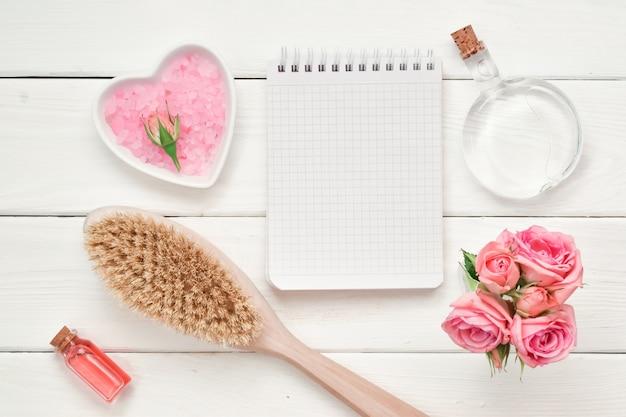 Cahier à carreaux et pinceau en bois avec cosmétiques et parfums