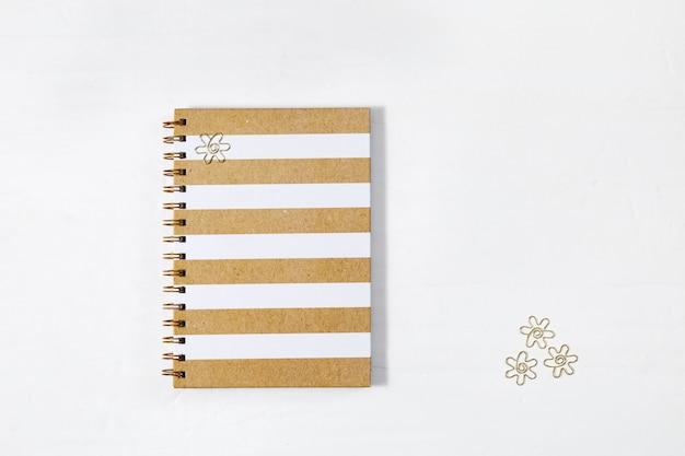 Cahier de classe fermé au printemps avec couverture lustrée et clips en métal doré sur le bureau blanc.