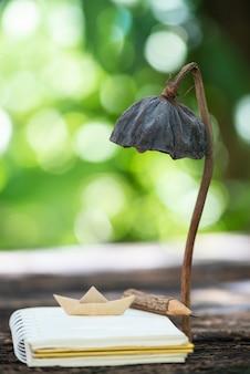 Cahier, crayon en bois, lampe de bateau en papier à partir d'une cosse de lotus séchée dans la nature.
