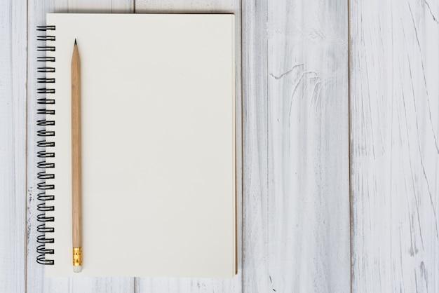 Cahier et crayon brun sur fond de table en bois
