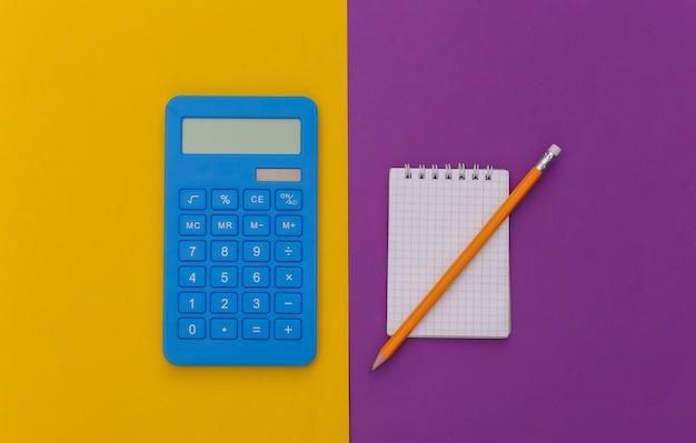 Cahier avec crayon, calculatrice sur fond jaune violet. vue de dessus