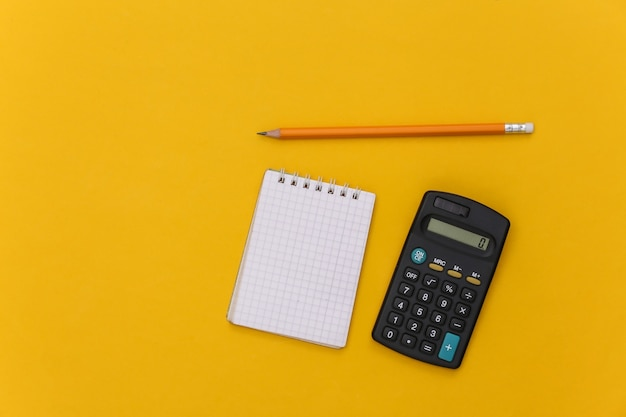 Cahier avec crayon, calculatrice sur fond jaune. vue de dessus